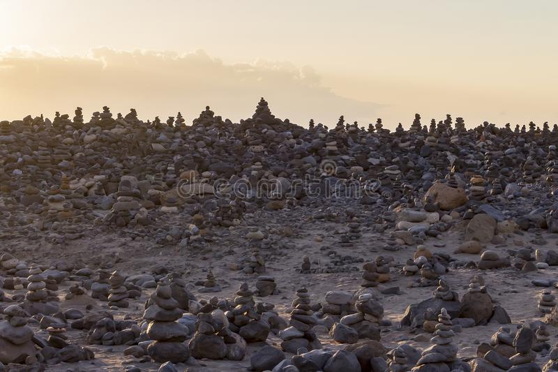 During sunset, the sun shines on the Cairns along the coast near La Caleta, Costa Adeje on Tenerife, Spain.  royalty free stock images