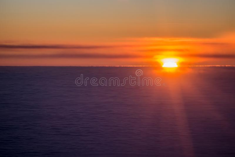 Sunset or sunrise from an airplane peeking through the clouds royalty free stock photos