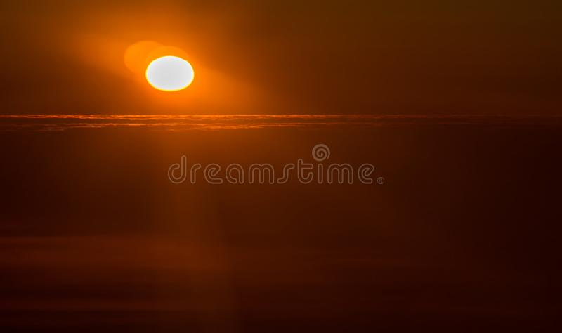 Sunset or sunrise from an airplane peeking through the clouds royalty free stock photo