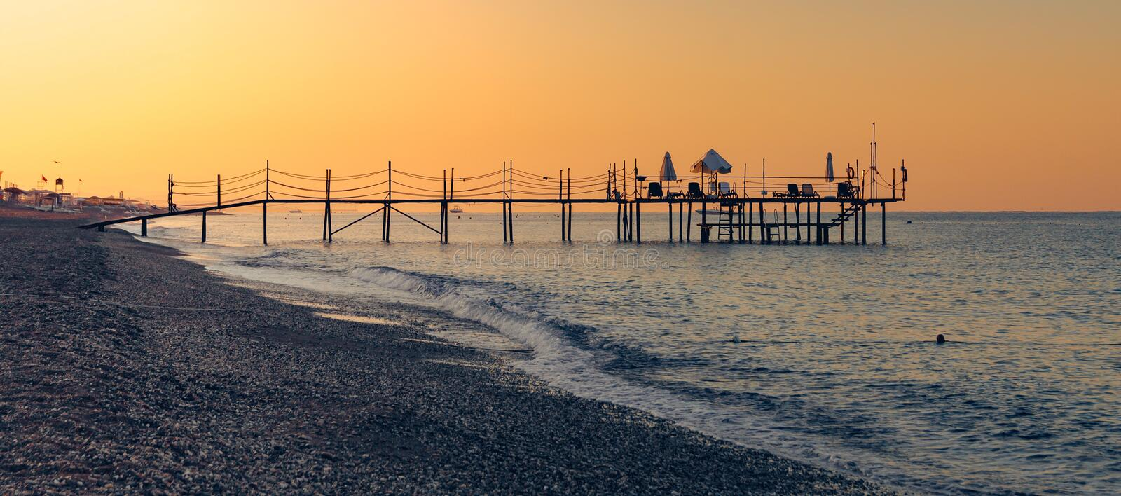Sunset or sunrise Scene at Tropical Beach Resort with wooden pier royalty free stock photo