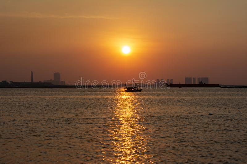 sunset on ancol beach Jakarta indonesia with beautiful yellow orange color sky stock photos