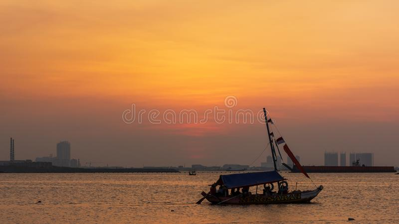 sunset with yellow orange color sky and silhouette of boat. Ancol beach, Jakarta, Indonesia stock photography