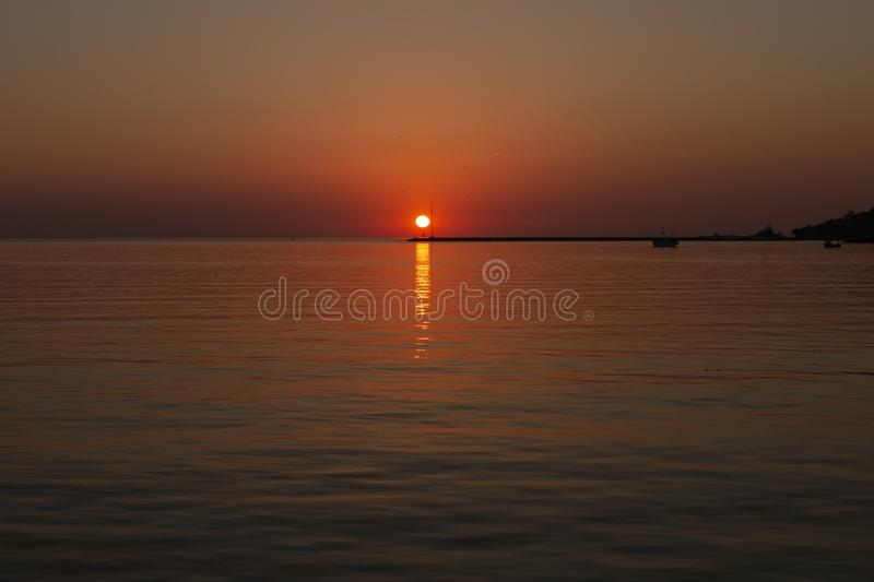 Sunset. Over a highly-populated city, accentuated by dust particles. Very clear and bright perspective with clouds layers that accentuate the horizon, while royalty free stock photography