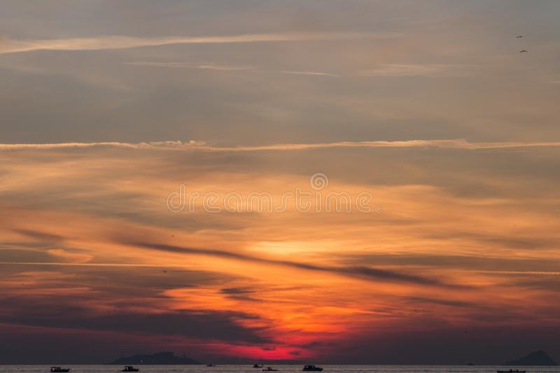 Sunset. Over a highly-populated city, accentuated by dust particles. Very clear and bright perspective with clouds layers that accentuate the horizon, while stock photos