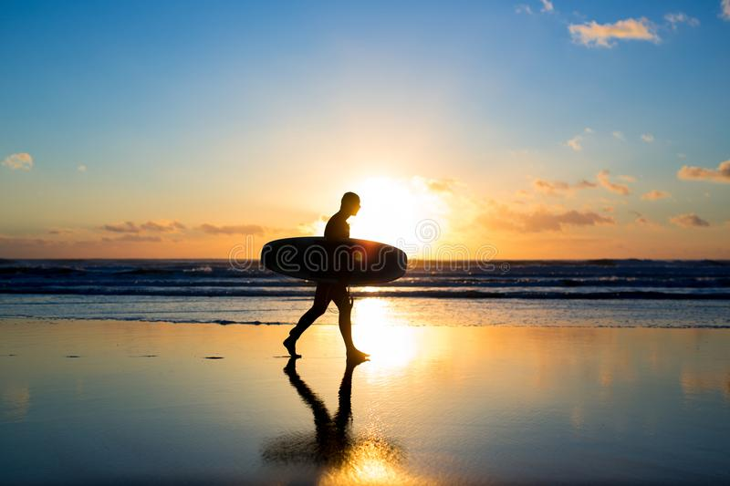 Sunset surfing. Silhouette of man surfer walking with a surf board in his hands across the ocean shore. Sunset surfing. Silhouette of man surfer walking with a stock image