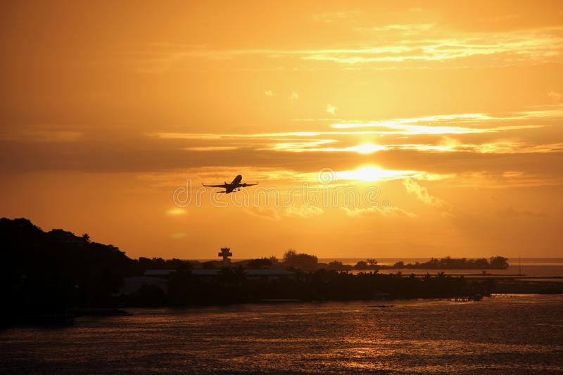 Sunset on Tahiti. During a stunning sunset a plane takes off from the airport of Papeete, Tahiti, French Polynesia royalty free stock photos