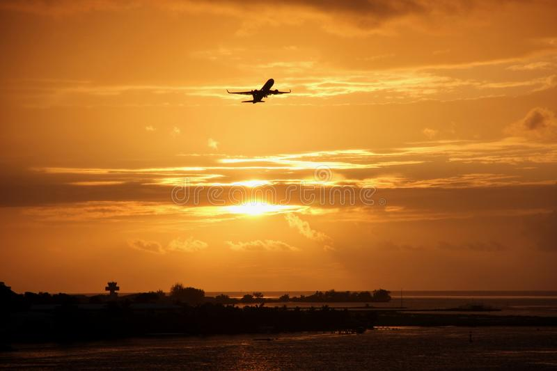 Sunset on Tahiti. During a stunning sunset a plane takes off from the airport of Papeete, Tahiti, French Polynesia royalty free stock photography