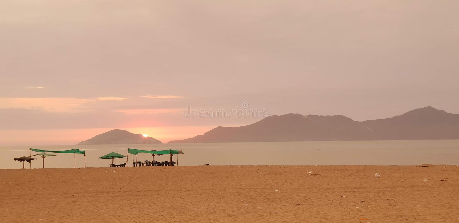 Sunset and tent in Besique Beach 2. Tent and food table in Sunset solitaire beach - Besique, Peru. Some mountains in the background royalty free stock photography