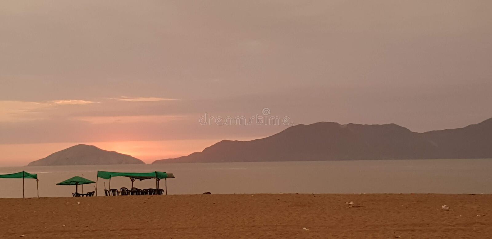 Sunset and tent in Besique Beach 3. Tent and food table in Sunset solitaire beach - Besique, Peru. Some mountains in the background royalty free stock photos