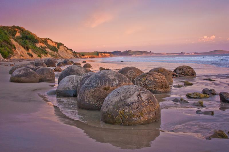 Sunset at th cost with famous rock formation of Moeraki Boulders, NZ. Pink sky above touristic popular place stock images