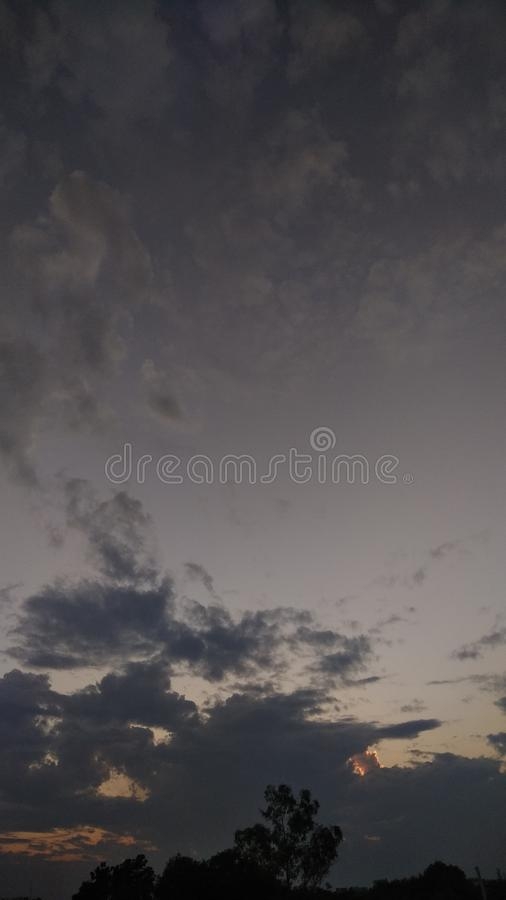 Sunset time dark grey clouds in the sky royalty free stock photos