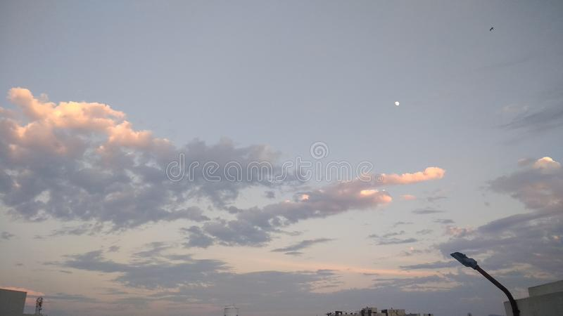 Sunset time orange clouds and moon in the sky stock photography