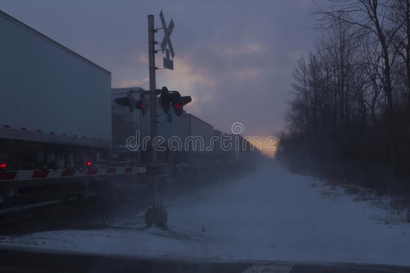 Sunset Train. A freight train approaches a crossing at a rural street in Western New York State. Image is shot in Winter against a sunset sky stock image