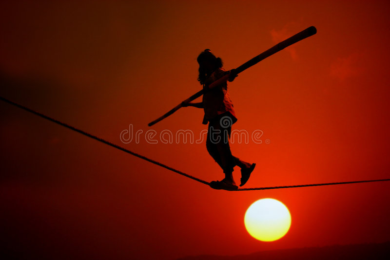 Sunset Trapeze. A silhouette of a poor girl working doing trapeze acts like walking on a rope on the side of a street at sunset stock photography