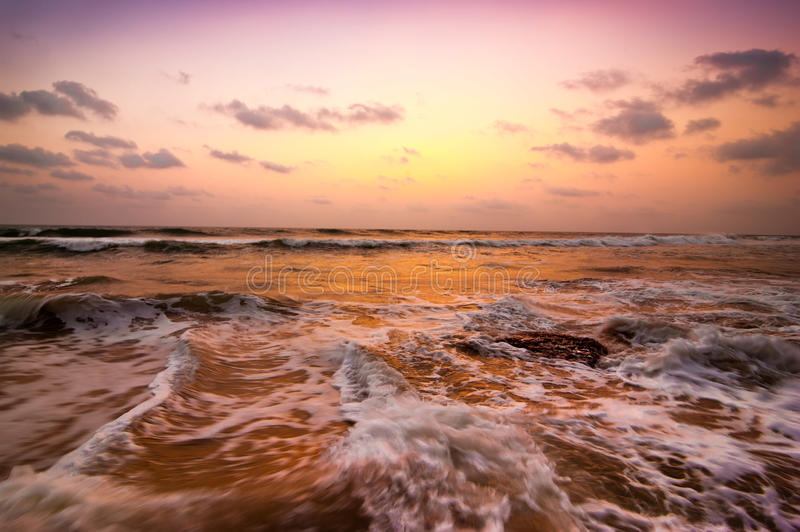 Sunset at tropical beach. Ocean sandy coast under evening sun royalty free stock images