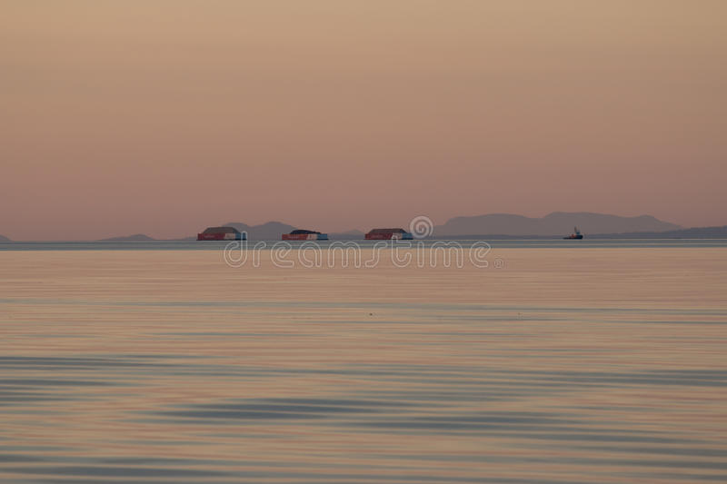 Sunset twilight ocean scene with tugboat and three barges in background stock photo