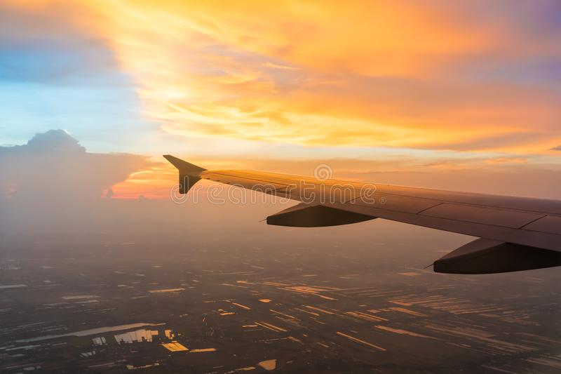 Sunset in twilight time with Wing of an airplane and cloud sky. Photo applied to tourism operators. royalty free stock images