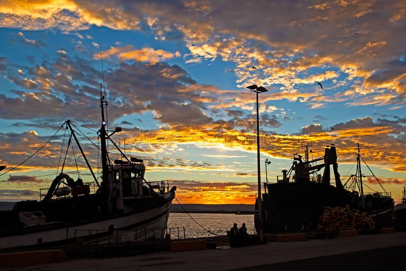 Sunset with two fishing boats in harbour stock photography