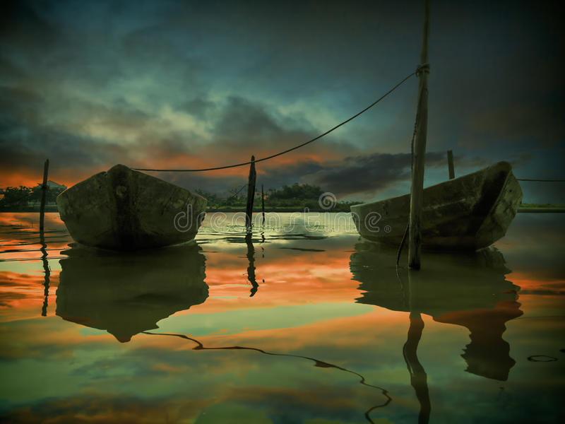 The sunset and two fishing boats royalty free stock images