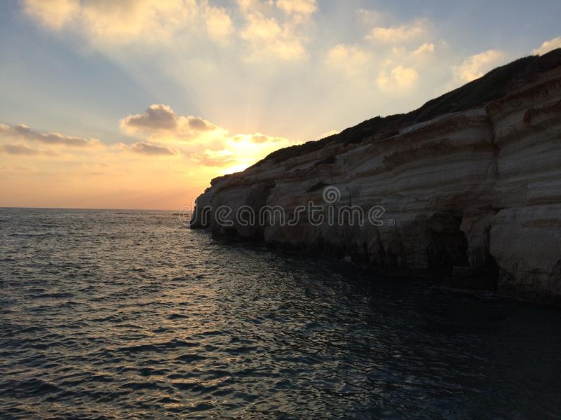 Sunset under the cloudy coast and sea stock photography