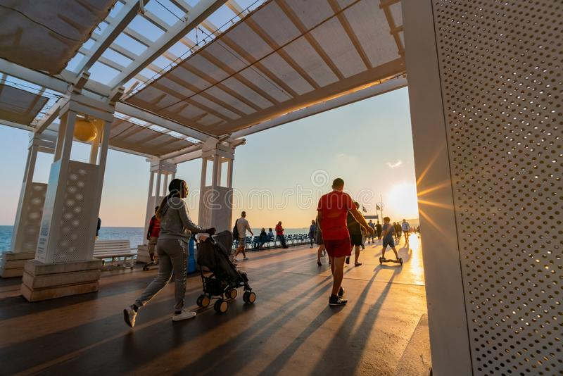 Sunset view of the beautiful Nice beach with many visitor walking around stock photos