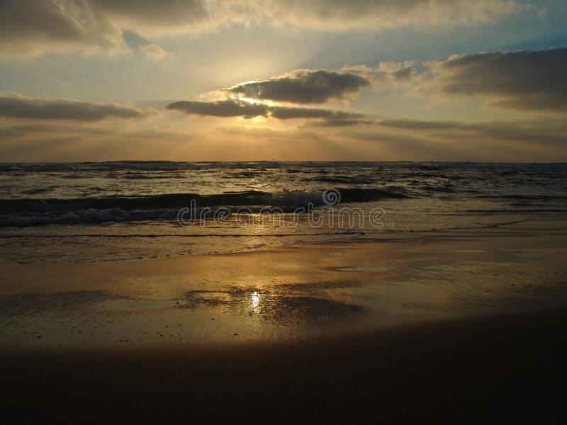 Sunset view on a calm sandy beach with cloudy sky and golden light stock image