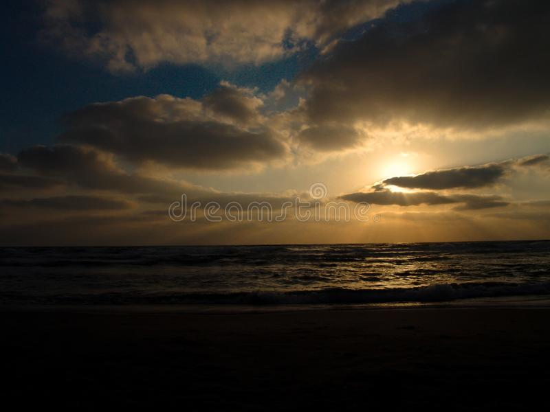 Sunset view on a calm sandy beach with cloudy sky and golden light stock photography