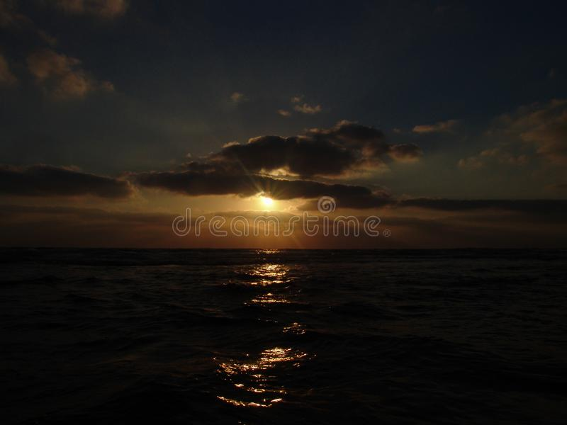 Sunset view on a calm sandy beach with cloudy sky and golden light stock photo
