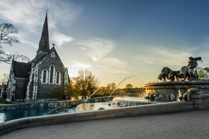 Gefion Fountain in front of St Alban`s Church in Copenhagen, Denmark. Sunset view of Gefion Fountain in front of St Alban`s Church in Copenhagen, Denmark royalty free stock photos