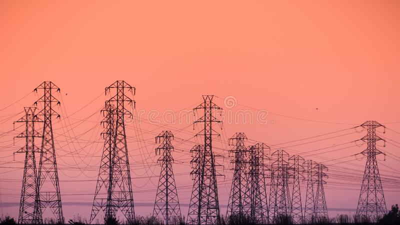 Sunset view of high voltage electricity towers on the shoreline of San Francisco bay area; California royalty free stock photo