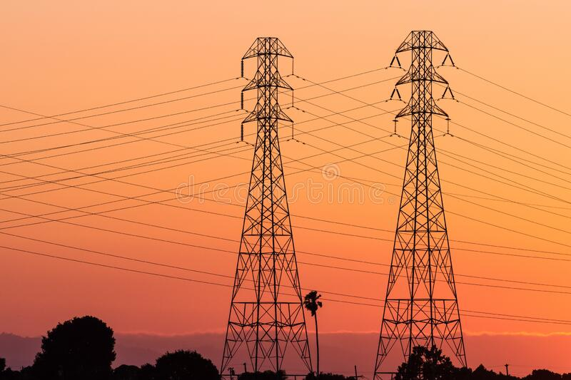 Sunset view of high voltage electricity towers on the shoreline of San Francisco bay area; California stock images