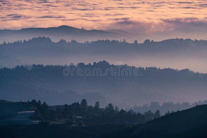 Sunset view of layered hills and valleys covered by a sea of clouds in Santa Cruz mountains ; San Francisco bay area, California stock images
