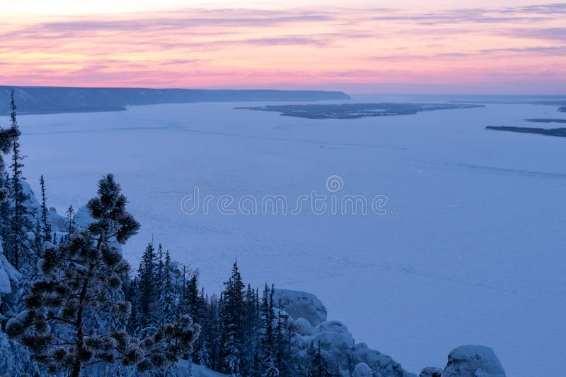 Sunset view on the Lena river in the Natural Park Lenskie Stolby Lena Pillars. Winter mountains landscape with trees and sunset. Stone Pillars in the Natural stock photo
