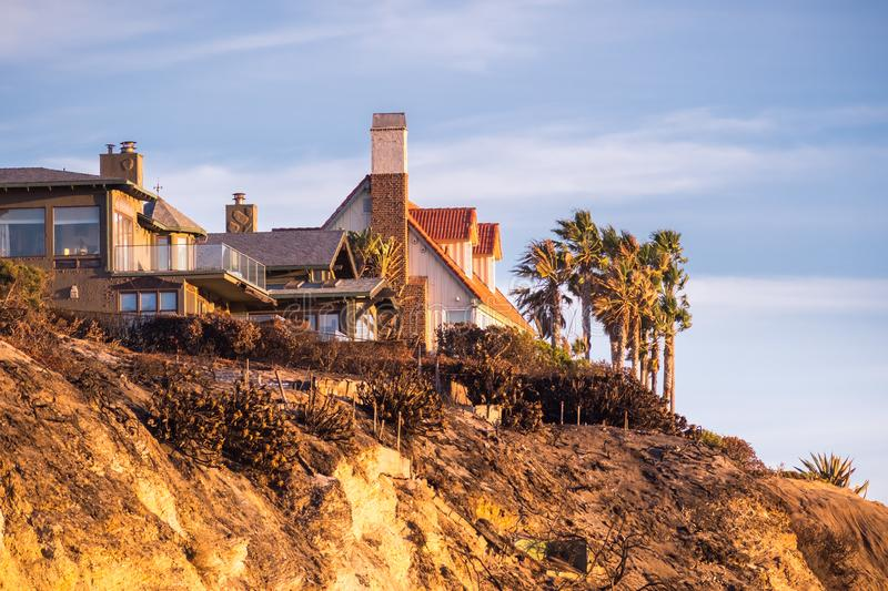 Sunset view of mansions built on top of cliffs on the Pacific Ocean coast, Malibu, Los Angeles county, California royalty free stock photos