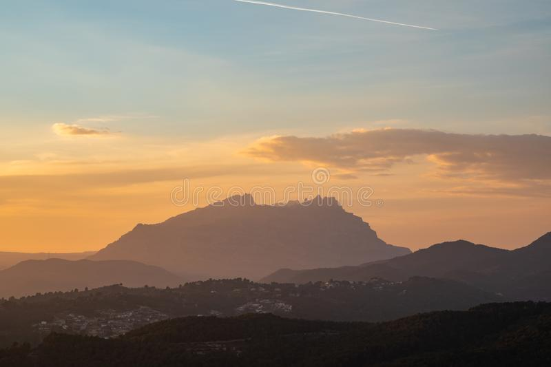 Sunset view of a mountain range with orange and blue sky. With copy space stock images