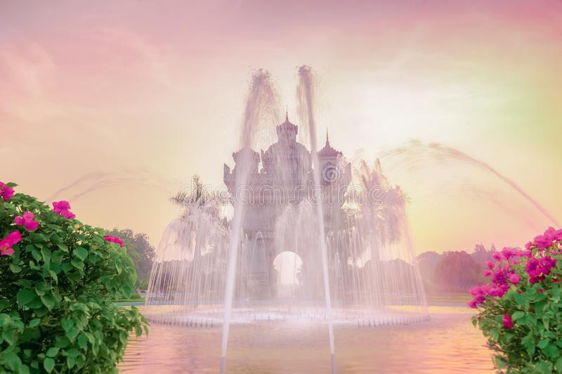 Sunset view of Patuxai arch or Victory Triumph Gate monument with fountain in front.  Vientiane, Laos travel landscape and stock photos