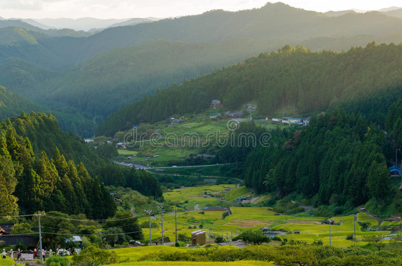 Sunset view with sun rays over countryside mountains, rice field royalty free stock photography