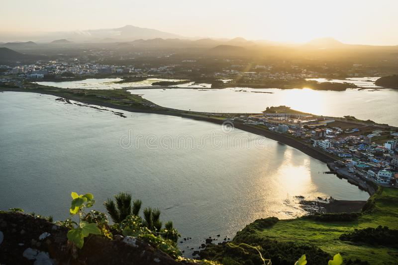 Sunset view to the volcanic landscape from Ilchulbong peak to Seongsan, Jeju Island, South Korea stock photos