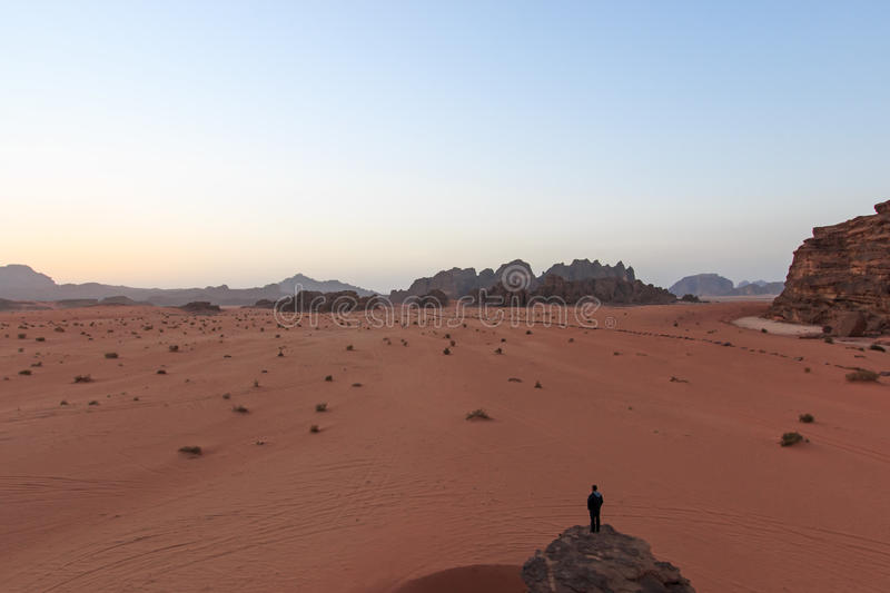 Sunset in the Wadi Rum desert, Jordan, with a man watching the scene from a rock on foreground stock images