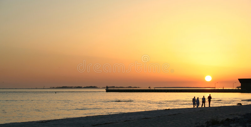 Sunset walk on the beach royalty free stock photo