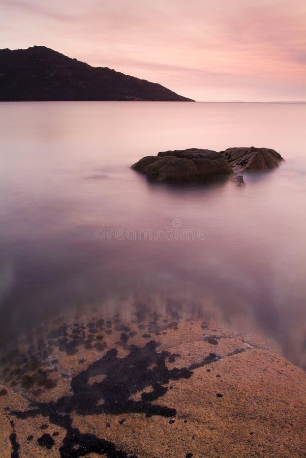 Sunset Water and Rocks. Pink sunset light on a coastal scene - Freycinet, Tasmania, Australia stock images