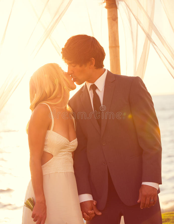 Sunset Wedding. Beautiful Sunset Wedding by the Sea. Bride and Groom Kissing at Sunset. Romantic Married Couple royalty free stock image