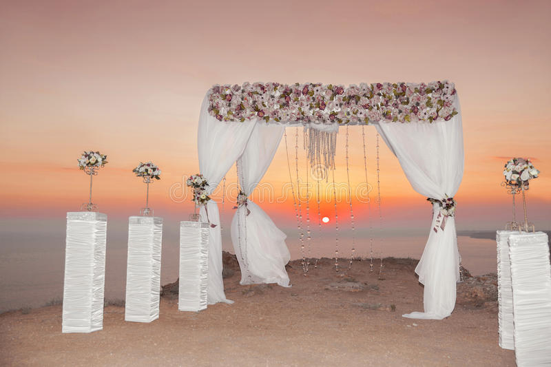 Sunset. Wedding ceremony arch with flowers decorative arrangement and white curtain on cliff above sea, sunrise outdoor summer ph royalty free stock photo