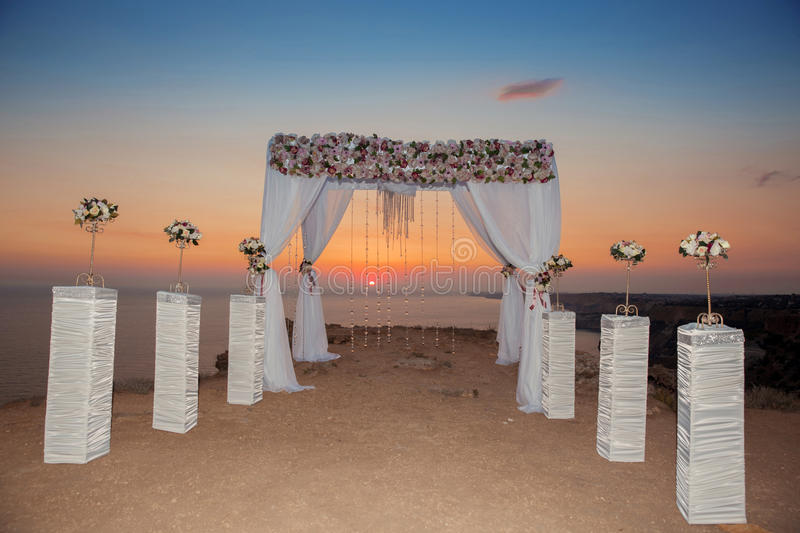Sunset. Wedding ceremony arch with flowers decorative arrangement with white curtain on cliff above sea, sunrise outdoor summer p royalty free stock photo