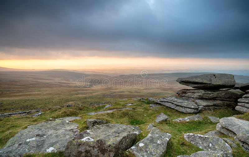 Sunset at West Mill Tor on Dartmoor. A storm brewing over West Mill Tor near Okehampton on Dartmoor National Park in Devon stock image