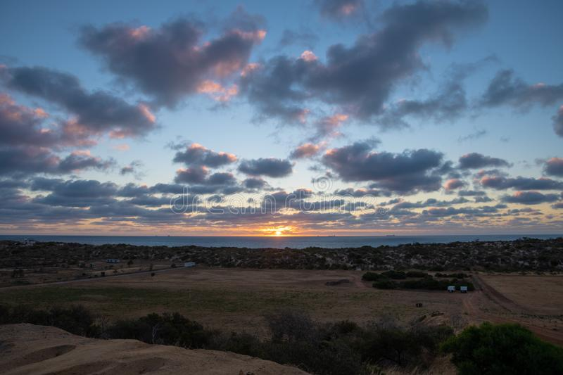 Sunset in Western Australia close to Geraldton with red colored tips of the clouds royalty free stock photo