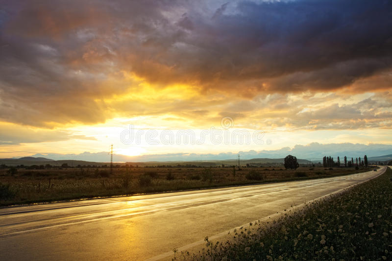 Sunset on wet road. Wet road after rain and sunset over fields stock images