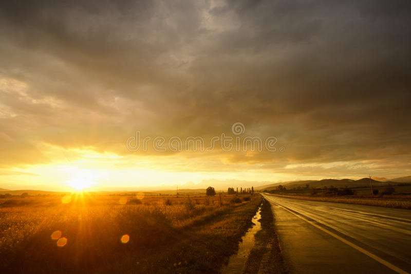 Sunset on wet road. Wet road after rain and sunset over fields royalty free stock image