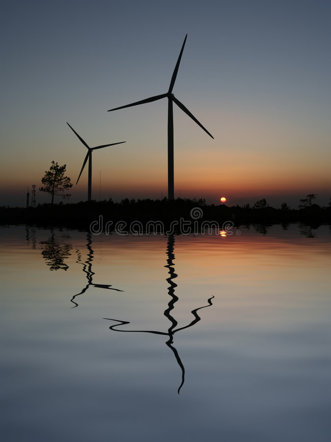 Sunset Wind Turbines. Reflected in the water royalty free stock image