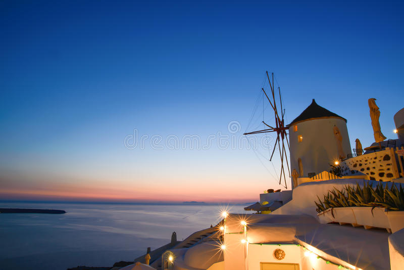 Sunset with the Windmill in Oia, Santorini, Greece. Sunset with the Windmill in Oia and the lighting of the city of Santorini, Greece in June 2015 stock images
